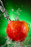 Fuji Apple Splash. A Delicoius Fuji Apple Being Splashed with Water over a Green Grandient Background Stock Images