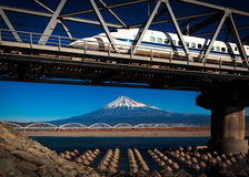 Fuji and Bullet Train. Mt.Fuji and a bullet train crossing the bridge on the river in japan Royalty Free Stock Images