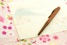 Fuji Mount pattern on letter paper and wood pen. On sakura pattern cloth Stock Photography