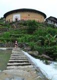 Fujian Tulou. Chuxi Tulou clusterr, Gril crosses old stone bridge Royalty Free Stock Photos