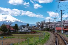 Fujikyu Railway train railroad track with snow covered Mount Fuji royalty free stock photography