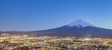 Fujiyoshida Town at night time with Mount Fuji. In winter season stock images