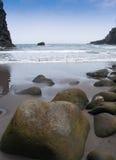 Fuktiga stenar på sandstranden Royaltyfria Foton