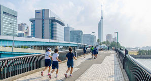 Fukuoka, Japan - June 30, 2014: Japanese high school students running in Momochi Beach road.This road heading to Fukuoka tower Stock Images