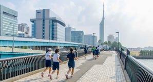 Fukuoka, Japan - Juni 30, 2014: Japanse middelbare schoolstudenten die in Momochi-Strandweg lopen Deze wegrubriek aan de toren va Stock Afbeeldingen
