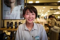 Fukuoka Japan - Maj 20: Den oidentifierade kvinnliga shoppingkontoristen ler på kameran i lager på Maj 20, 2017 i Fukuoka Arkivbild