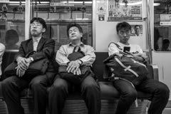 Fukuoka Japan - Maj 19: Oidentifierade trötta män i en spårvagn på Maj 19, 2017 i Fukuoka, Japan Fotografering för Bildbyråer