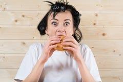 Ful kvinna som äter en hamburgare fotografering för bildbyråer