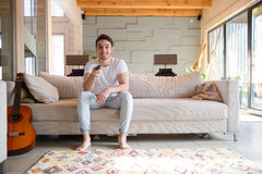 Ful-length shot of man using remote controller. Full-length shot of man sitting on couch and using remote controller Stock Photos