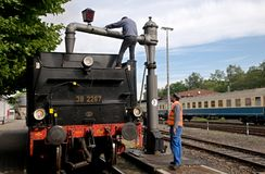 Fulfilling the steam locomotive water. Steam locomotive  in the depot -  water filling Stock Photography