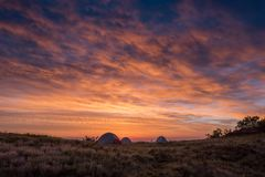 Fulgor alaranjado brilhante das nuvens acima de três barracas Fotografia de Stock Royalty Free