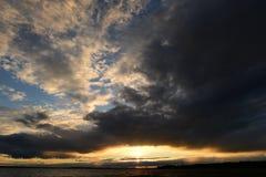 Fulgor da luz solar nas nuvens escuras do céu no por do sol Foto de Stock