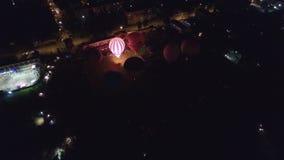 Fulgor do balão de ar quente da noite e dança aéreos no Kungur, Rússia filme