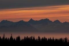 Fulgor do por do sol sobre picos de montanha em uma baía nevoenta foto de stock royalty free