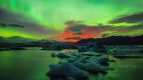 Fulgor verde de néon brilhante incrível do aurora borealis da luz do norte no céu noturno polar escuro sobre o lago na opinião de video estoque