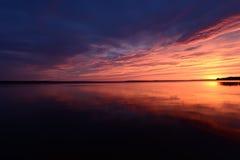 Fulgor vermelho do por do sol sobre o lago tarde na noite do verão Fotografia de Stock
