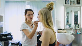 Fulländande handlag I salongen för härliga blondiner gör makeup Makeupkonstnären målar hennes kanter, ökar beloppet av stock video