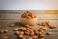 Full of Almonds in wooden brown bowl. On wooden background Royalty Free Stock Image