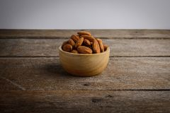 Full of Almonds in wooden brown bowl. On wooden background Royalty Free Stock Photos