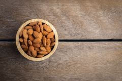 Full of Almonds in wooden brown bowl. Top view of Full of Almonds in wooden brown bowl on wooden background Stock Images