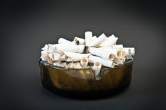 Full ashtray with butts over black Stock Photo