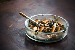 Full ashtray and cigarette Royalty Free Stock Photography