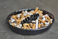 Full ashtray of cigarettes on table, close-up.  Royalty Free Stock Photos