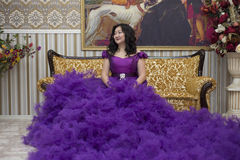 Full Asian woman in a lush lilac dress. Full Asian woman in a lush lilac dress sitting on the couch in the living room Royalty Free Stock Photography