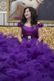 Full Asian woman in a lush lilac dress. Full Asian woman in a lush lilac dress sitting on the couch in the living room Stock Images