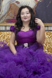 Full Asian woman in a lush lilac dress. Full Asian woman in a lush lilac dress sitting on the couch in the living room Royalty Free Stock Photo