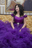 Full Asian woman in a lush lilac dress. Full Asian woman in a lush lilac dress sitting on the couch in the living room Stock Image