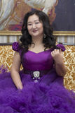 Full Asian woman in a lush lilac dress. Full Asian woman in a lush lilac dress sitting on the couch in the living room Stock Photo