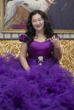 Full Asian woman in a lush lilac dress. Full Asian woman in a lush lilac dress sitting on the couch in the living room Stock Photos