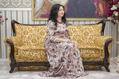 A full Asian woman sitting on the sofa in the living room. Royalty Free Stock Photo