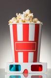 Full ask av popcorn och exponeringsglas 3D på en grå färg Royaltyfri Foto