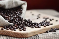 A full bag of brown coffee beans lies on a wooden surface. Attributes related to the preparation of natural coffee Stock Images