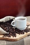 A full bag of brown coffee beans and a white cup of hot coffee l. Ies on a wooden surface. Attributes related to the preparation of natural coffee Royalty Free Stock Photography