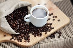 A full bag of brown coffee beans and a white cup of hot coffee l. Ies on a wooden surface. Attributes related to the preparation of natural coffee Stock Photos