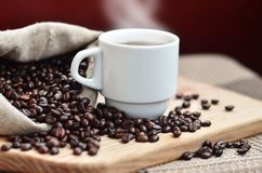 A full bag of brown coffee beans and a white cup of hot coffee l. Ies on a wooden surface. Attributes related to the preparation of natural coffee Stock Photography