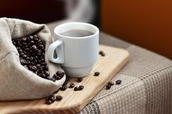 A full bag of brown coffee beans and a white cup of hot coffee l. Ies on a wooden surface. Attributes related to the preparation of natural coffee Stock Photo