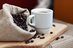 A full bag of brown coffee beans and a white cup of hot coffee l. Ies on a wooden surface. Attributes related to the preparation of natural coffee Stock Images
