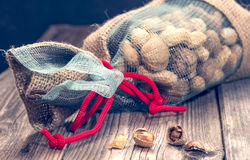 Full bag of nuts. Broken nuts and one full bag of them royalty free stock image