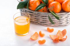 Full basket of mandarin with a glass of juice. Juicy tangerines with green leaves orange background white clementine fresh fruit citrus ripe food mandarins royalty free stock photos
