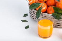Full basket of mandarin with a glass of juice. Juicy tangerines with green leaves orange background white clementine fresh fruit citrus ripe food mandarins royalty free stock photo