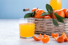 Full basket of mandarin with a glass of juice stock photo