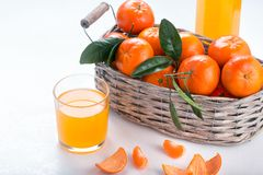 Full basket of mandarin with a glass of juice royalty free stock photography