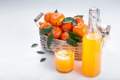 Full basket of mandarin with a glass of juice royalty free stock images