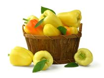 Fresh sweet peppers with leaves in a wooden basket. Isolated. Ta stock images