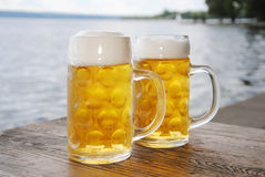 Full Beer Mugs. Two Beer Mugs with fresh beer and foam  outside in a beergarden at lake Stock Image