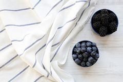Full blue bowls of berries on a white wooden surface, top view. Summer berry. From above, overhead. Flat lay Stock Photos